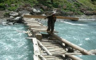 Braving the odds: These women cross turbulent water currents while ferrying firewood on their shoulders in north Kashmir