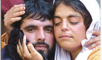 A woman cries as she hugs her brother after his surrender in Rampur