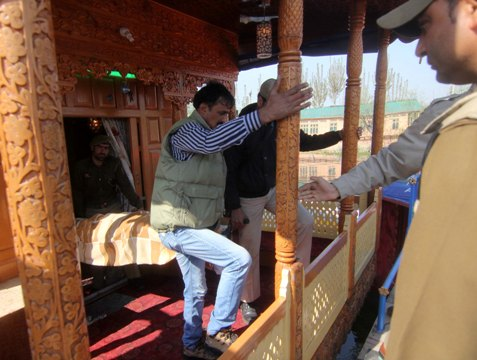 HORROR: The body of the murdered woman wrapped in a blanket is taken out of the houseboat for post-mortem examination by the J&K police personnel.