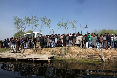 SCENE: Eager onlookers watch the body being brought from other side of Dal in a motorboat to be taken to Rainawari hospital in an ambulance parked nearby.