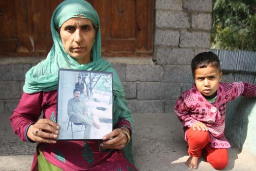 Widow of Farooq Ahmad Shiekh holding her husband's photograph. Pic: Bilal Bahadur