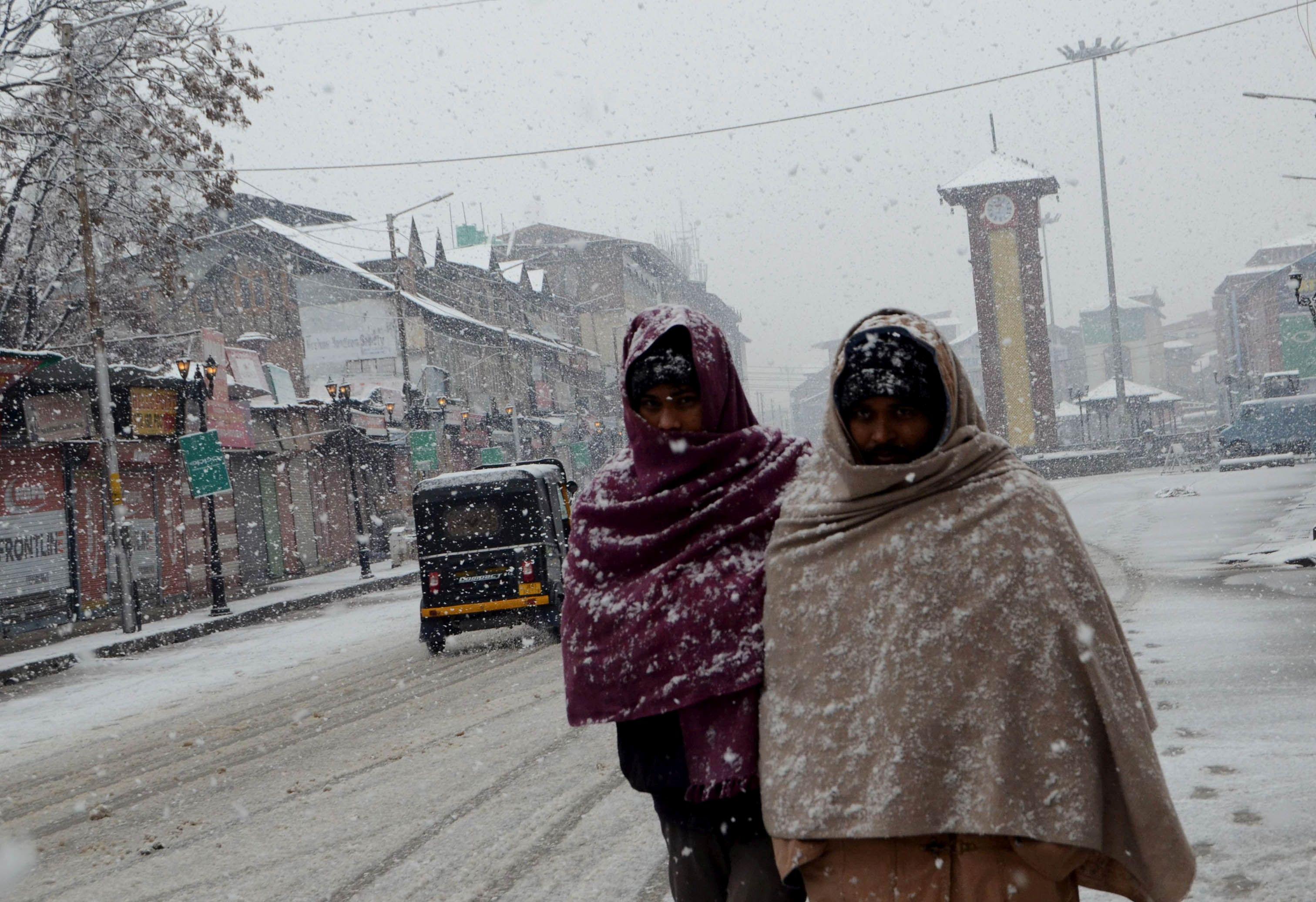 Non-local workers walking at Lal Chowk amid snowfallKL image by Bilal Bahadur