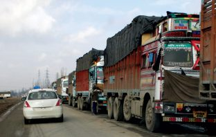 Long line of stranded trucks on a road. KL Image by Bilal Bahadur