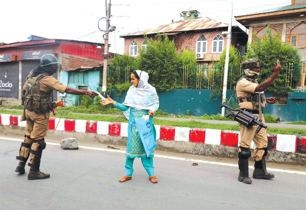 CRPF checking the medical documents of a woman during restrictions in old city of Srinagar. KL Image by Bilal Bahadur